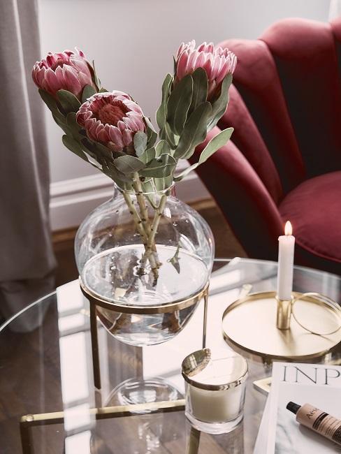 Mehrere Protea Pflanzen im Strauß auf Tisch neben Kerze