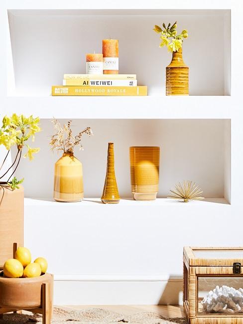 Gelbe Dekoelemente in weißer Wand