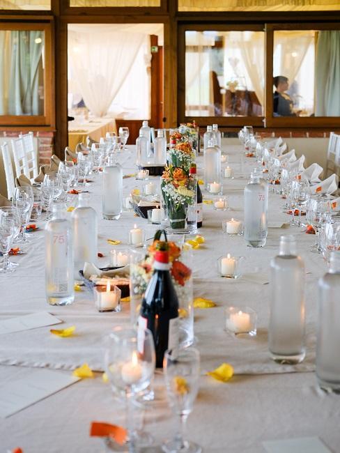 Blumen Tischdeko mit einzelnen Vasen und Blumen auf gedecktem, weißen Tisch