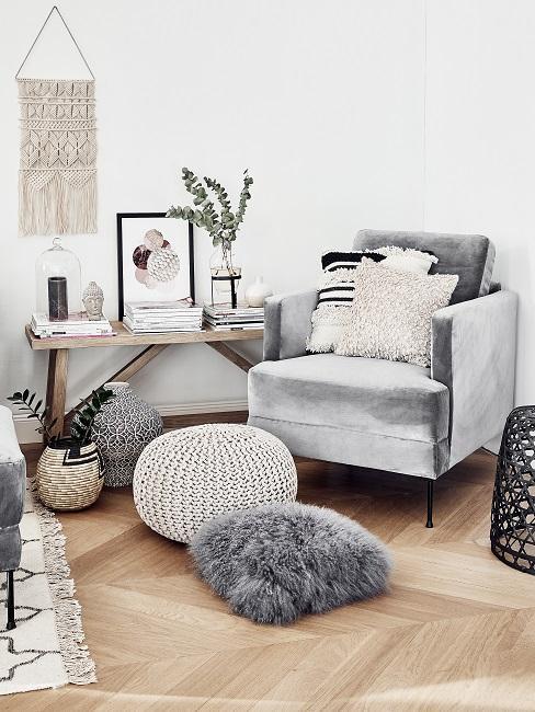 Helles Wohnzimmereck in Beige und Grautönen, ein Sessel aus grauem Samt mit Kissen vr einem Holztisch mit Deko und Büchern, darüber ein Wand-Makramee, auf dem Boden ein Teppich und seitlich Kissen sowie ein Pouf