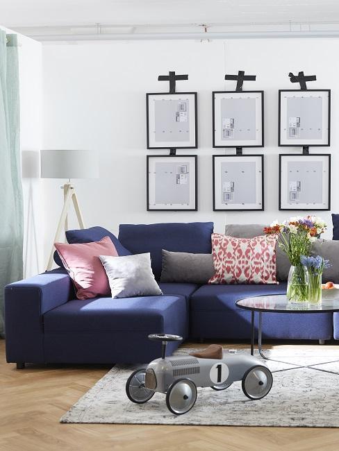 Wohnzimmer mit einem Textilsofa in Blau und vielen bunten Kissen als günstige Deko
