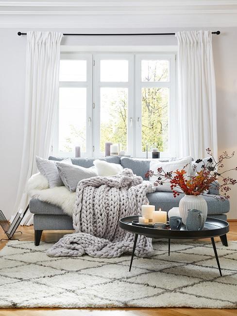 Sofa im Wohnzimmer mit Kissen und Strick-Plaid
