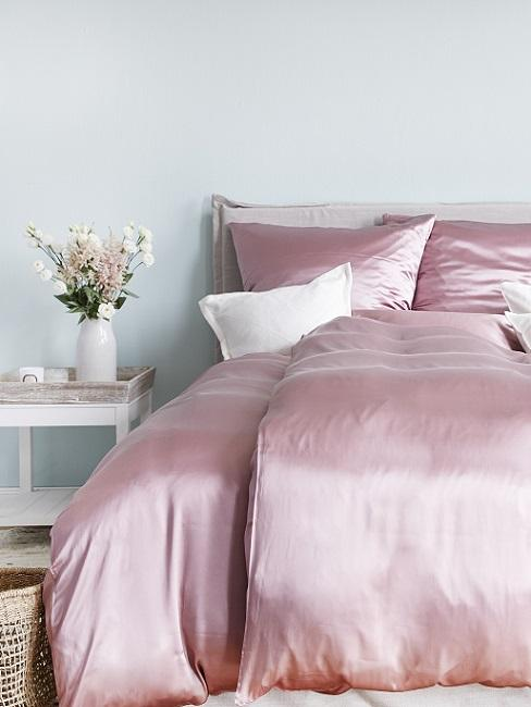 Bett mit Bettwäsche aus glänzender Seide in Rosa