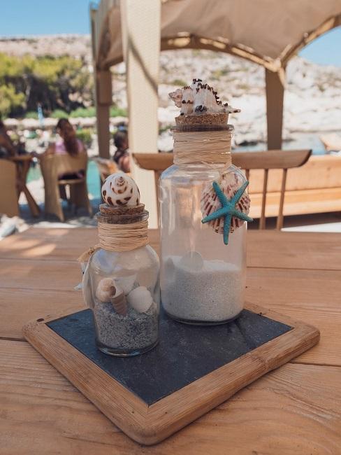 Zwei Flaschen auf einem Brett gefüllt mit Sand und Muscheln und auch außen mit Muscheln dekoriert