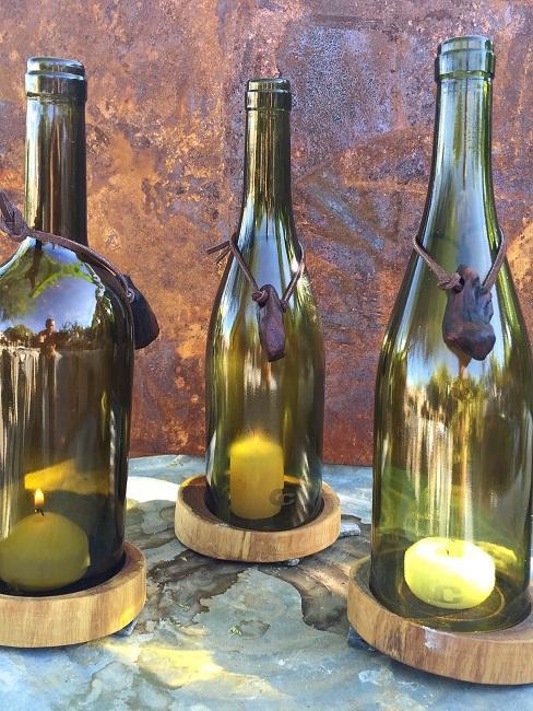 Untersetzer aus Holz mit Kerzen und darüber grüne Flaschen