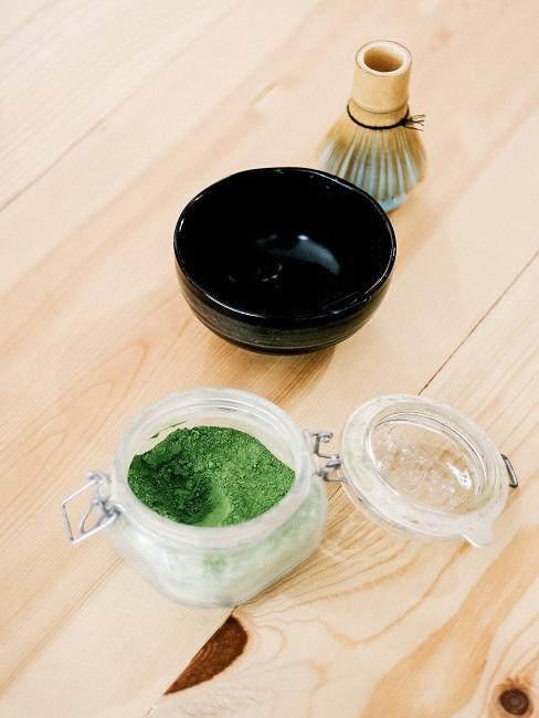 Teezeremonie schwarze Teeschale neben Matchapulver und Bambusbesen