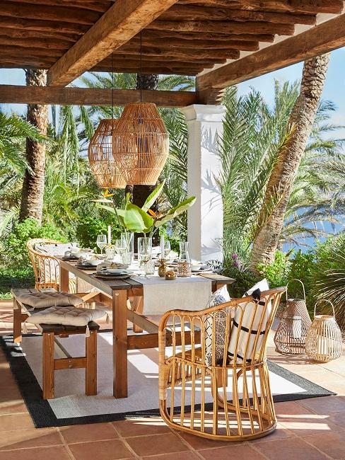Kolonialstil überdachte Terrasse mit Tisch und Stühlen aus Holz und Lampen aus Bambus