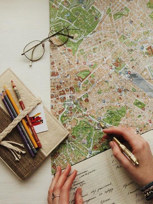 Karte und Buch neben Stiften auf Tisch