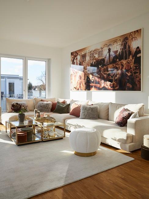 Großes Wohnzimmer mit weißer Couch und goldenen Elementen
