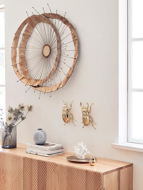 Wand mit Wandobjekten aus Holz und in Gold