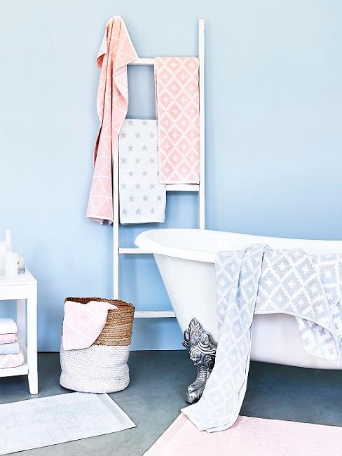 Hellblaue Wandfarbe im Badezimmer mit Badewanne, Leiter und Dekokorb