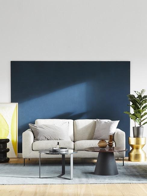 Blaue Wand mit weißer Wandfarbe kombiniert und grauem Sofa