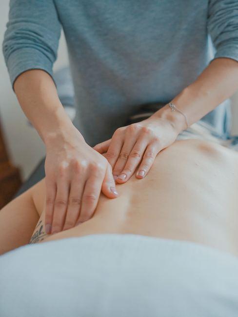 Persona dando un masaje a otra en la espalda