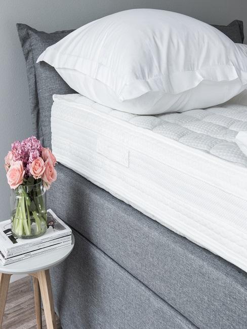 cama matrimonial gris con un colchón grueso