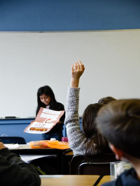 Niña presentando un proyecto en un aula mientras otra niña levanta un brazo para pedir palabra
