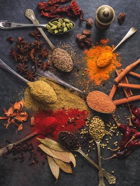 Especias asiáticas en grano y en polvo dispuestas sobre cucharas y una superficie oscura