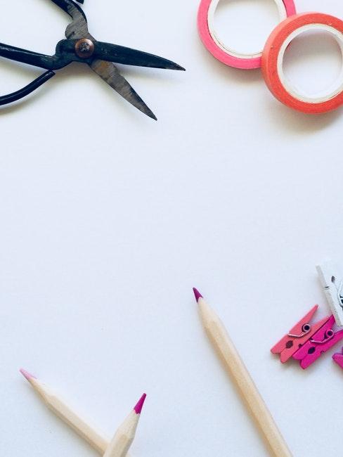 Paire de ciseaux noir, crayons roses et rubans adhésifs rose et orange