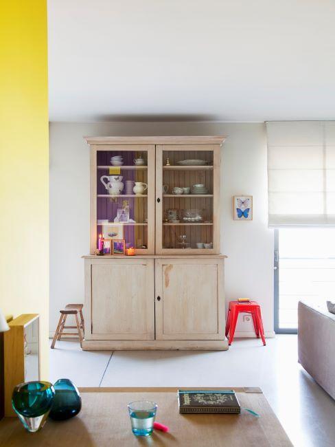 Salon avec mur jaune, buffet en bois naturel clair et tabouret rouge