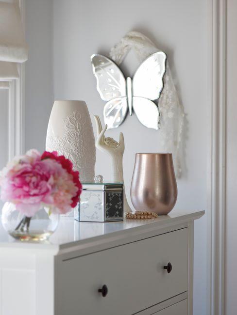 Boite à bijoux en verre miroir sur commode blanche avec vases et papillon mural décoratifs