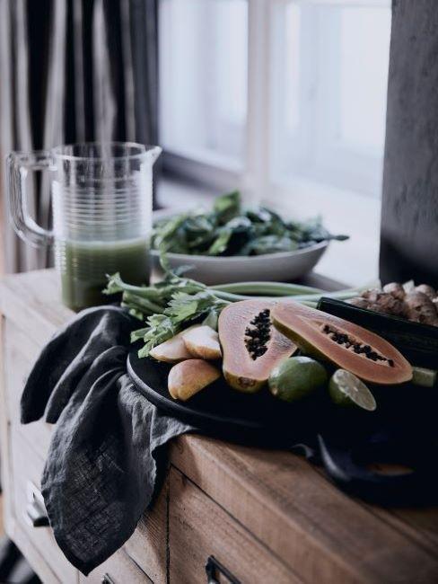 caraffa con estratto di frutta e piatto con frutta fresca