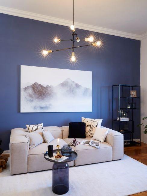 soggiorno con parete di colore blu e divano chiaro