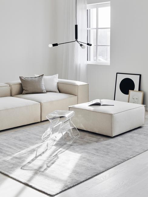 Woonkamer in minimalistische stijl met witte bank en hokker en grijsvloerkleed
