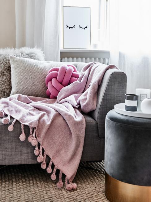 Jasny salon z szarym pufem, kanapą, na której leży różowy koc oraz poduszka supeł