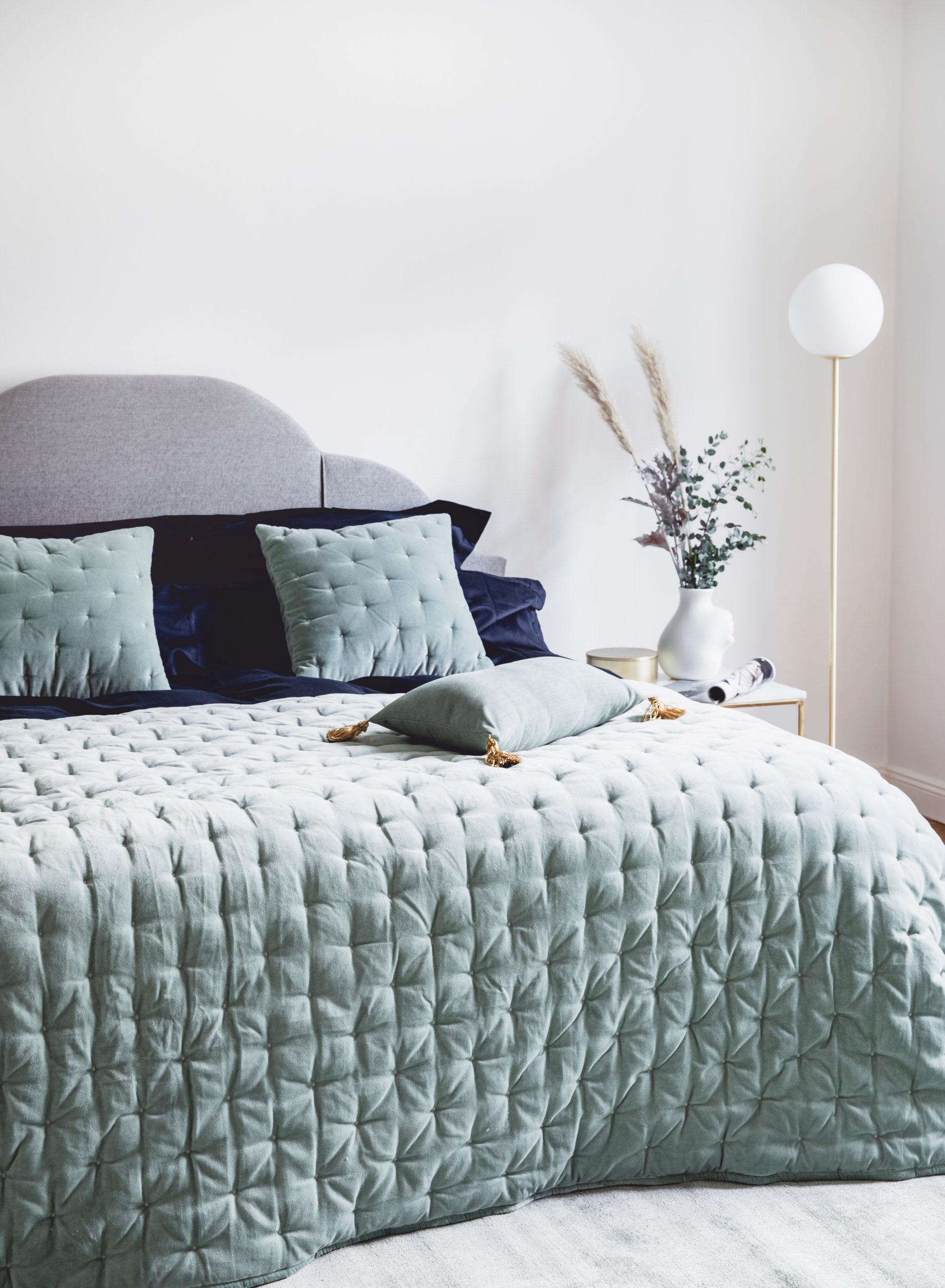 Szara sypialnia z podwójnym łóżkiem zaścielonym kapą w kolorze szałwiowej zieleni
