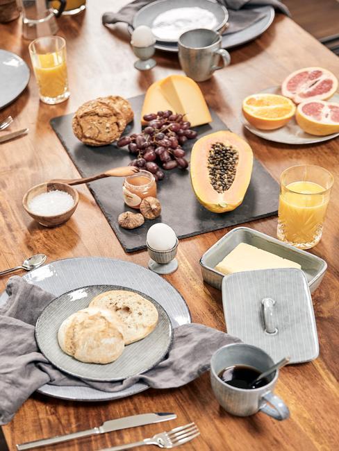 Stół z szarą, zastawą kuchenną oraz przezroczystymi szklankami