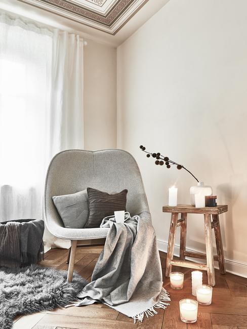 Szary fotel z poduszkami i kocem, obok zapalone świece