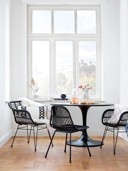 Jadalnia z czarnym stołem i krzesłami zaaranżowana w wykuszu