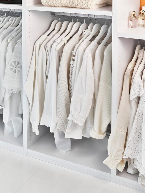 Białe, damskie bluzki równo powieszone w szafie