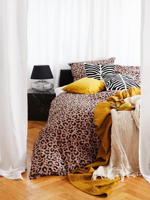 Łóżko w sypialni z pościelą w zwierzące wzory i żółte poduszki