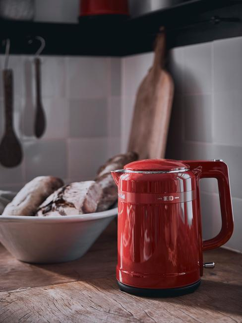 Czerwony czajnik stojący na blacie obok koszyka na chleb