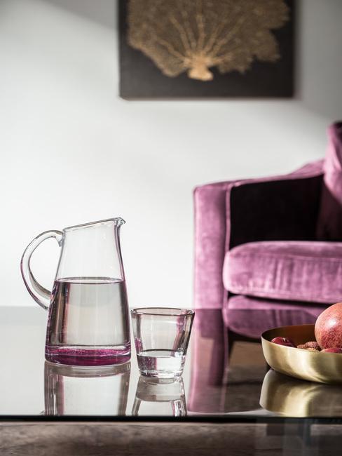 Salon w stylu glamour ze szklanym stolikiem kawowym oraz jasno bordowa sofą
