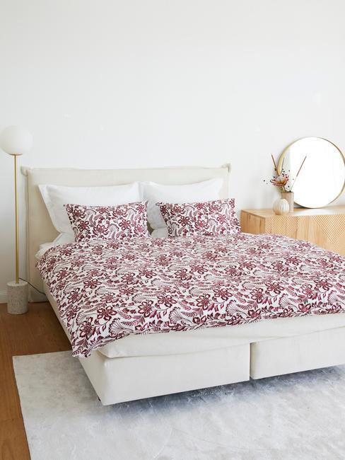 Jasna sypialnia z podwójnym łożkiem, drewnianym lustrem oraz czerwoną, wzorzystą narzutą na pościel