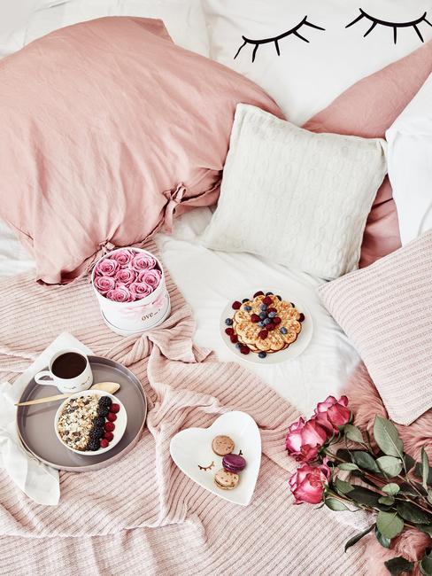 Łóżko z różowym kocem, różowymi poduszkami oraz białymi poduszkami