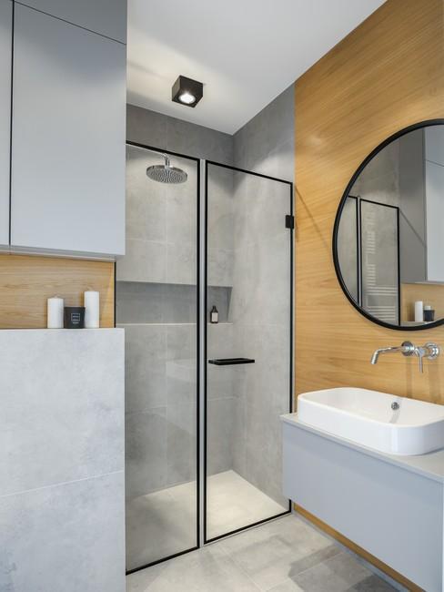 Nowoczesna łazienka z elementami drewna i czarnym wykończeniem.