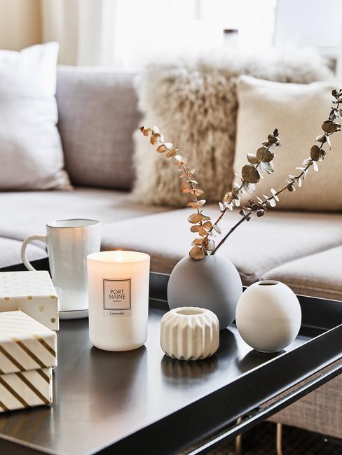 Salon z kanapą z poduszkami dekoracyjnymi oraz stolikiem kawowym ze świeczkami