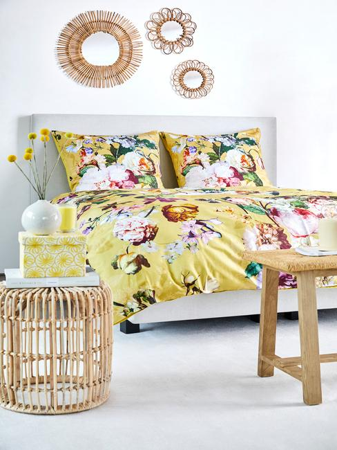 Biała sypialnia z żółtą pościelą, drewnianymi meblami oraz ozdobami na ścianie