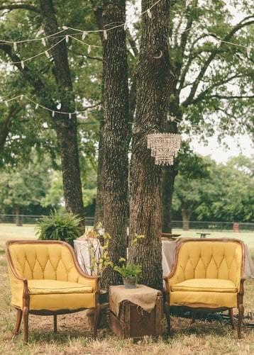 Dwa żółte, tapicerowane krzesła pod drzewem