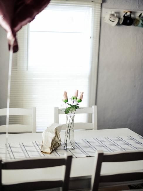 Wnętrze jadalni ze stołem, na któym jest wazon z kwiatami