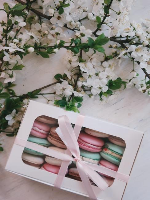 Pudełko z makaronikami oraz kwiaty leżące na stole