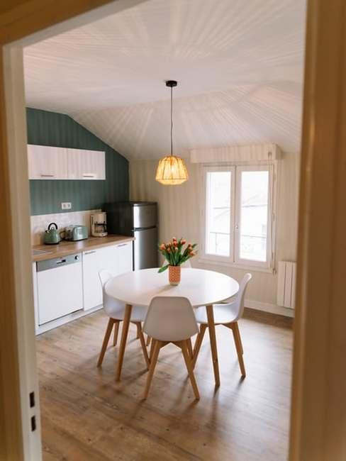 Kuchnia na poddaszu z okrągłym stołem i krzesłami, z pomalowaną jedną ścianą