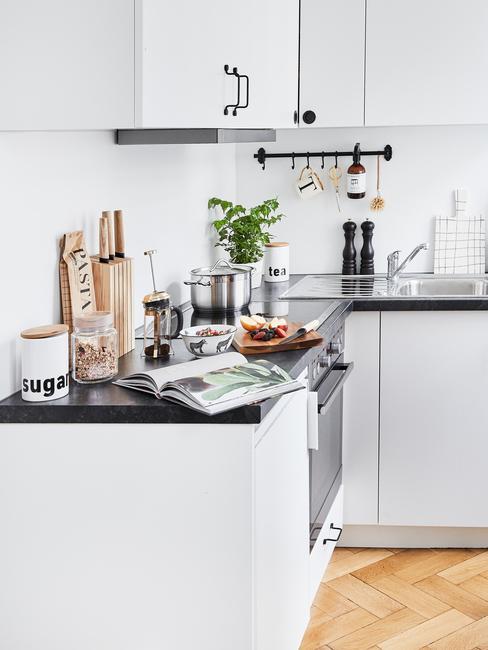 Biała kuchnia z drewnianą podłogą oraz akcesoriami kuchennymi