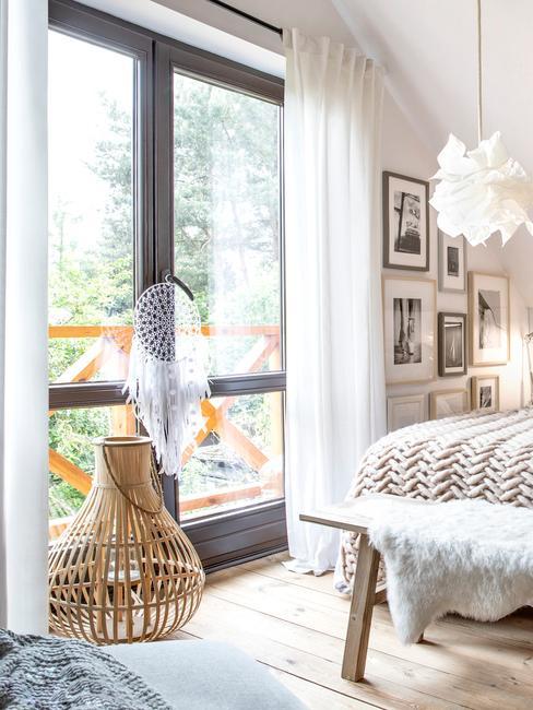 Fragment sypialni w stylu boho z dekoracyjnym koszykiem oraz łapaczem snów przy oknie