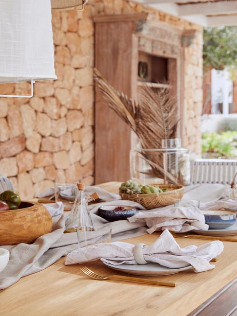 Ceramiczna zastawa na drewnianym stole, lniane serwetki i złote sztućce
