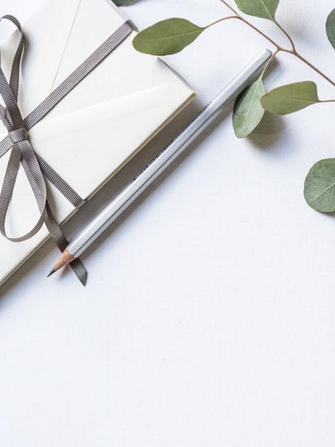 Zaproszenie ślubne, ołowek oraz płatki roślin lezące na stole