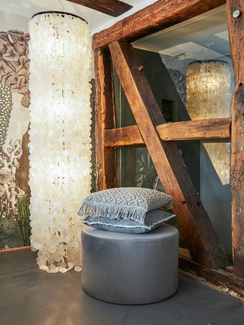 Szary puf stojący przy drewnianych słupach w pomieszczeniu