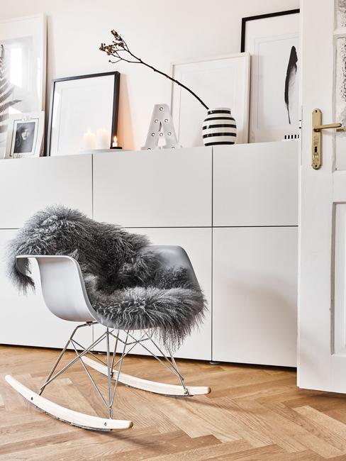 Biała komoda z dekoracjami oraz fotel bujany z kocem